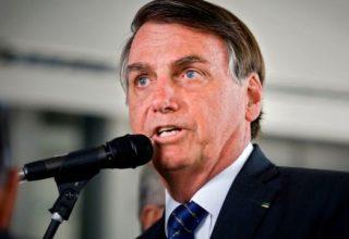 Bolsonaro fala ao microfone, o equipamento está em um pedestal e ele usa terno preto